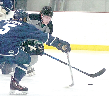 Staff photo by Steve Muscatello New Ulm Steel forward Fritz Belisle tries to get past and Alexandria defender during the first period Saturday at the New Ulm Civic Center. For more photos of this event go to cu.nujournal.com