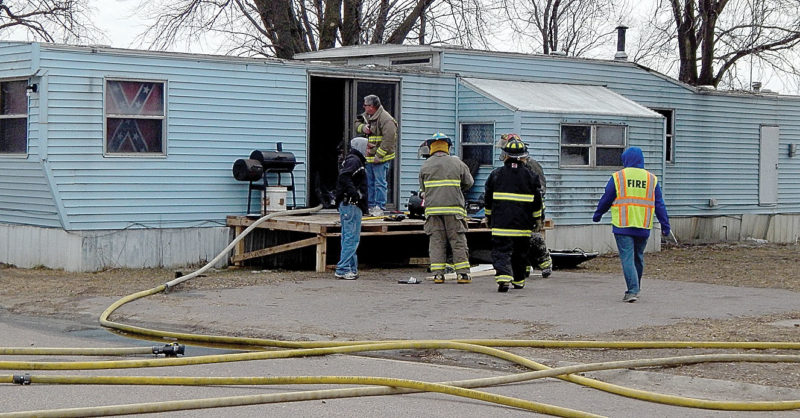 Staff photo by Kevin Sweeney New Ulm firefighters go through the trailer home damaged by fire at Skyview Trailer Park near New Ulm on Saturday. No one was in the home at the time.