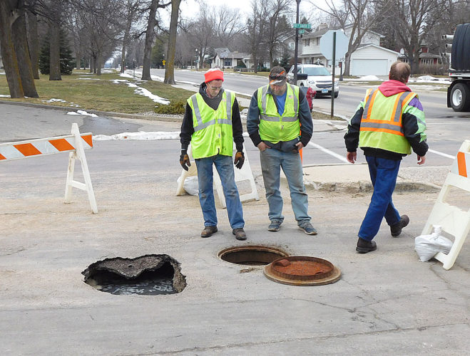 New Ulm utilities workers check out the sinkhole on 10th South and Summit Street caused by a sewer main break.