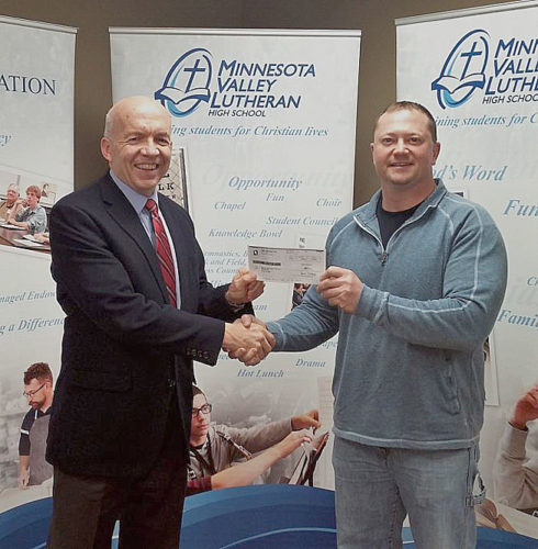 Tim Plath of MVL Schools accepts a donation check for $1,000.00 from New Ulm Quartzite Quarries Manager Andrew Gieseke. The school will use this donation towards it office remodeling project this upcoming summer.