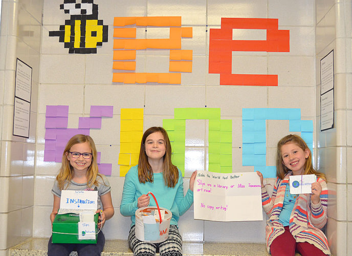 "Staff photo by Connor Cummiskey The three third-grade girls behind the ""Feel Better"" postcards at Jefferson Elementary School sit in front of a ""Bee Kind"" mural with their drop boxes and postcards. Pictured from left to right: Kelsey Grosam, Grace Bregel and Maarit Mattson."