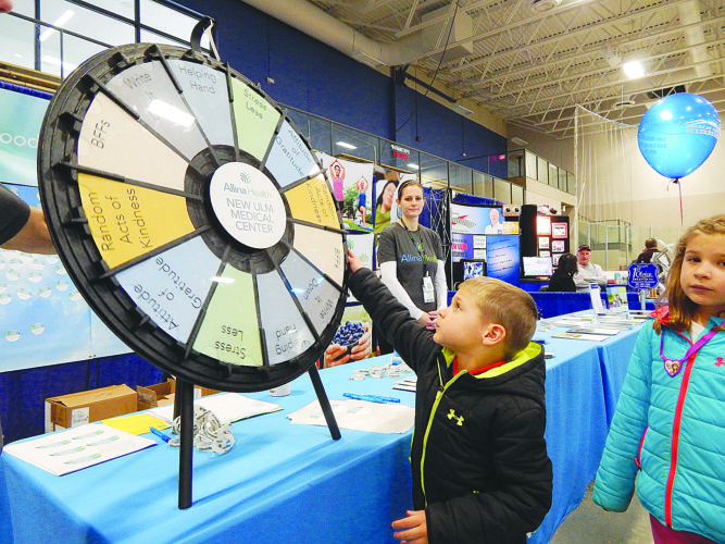 Bayler, left, and Brendley Nordby of New Ulm spin the wheel at the Allina Health booth at the New Ulm Health & Home Show Sunday.
