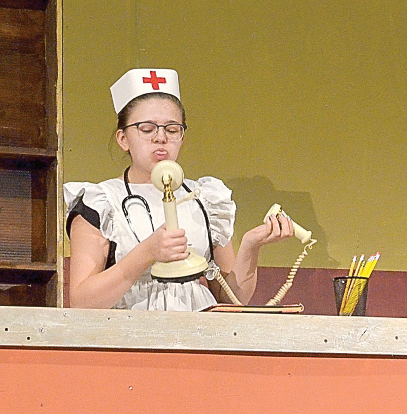 Staff photos by Connor Cummiskey Nurse Hilda Hatchet (Abby Hietala) blows a raspberry after getting of the phone with Lotta Cash (Siiri Rakowski) who is coming to visit the clinic.