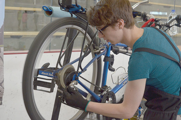 Staff photo by Connor Cummiskey Founder and owner of Andy's Bike Shop Andrea Hoffmann checks the shifting mechanism on a bike at the New Ulm Bike Expo Saturday.