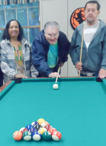 Submitted Photo Enjoying a new pool table Ronald Lyman (center) recently donated to the Dunkirk Adult Day Care Center are Maria Martinez (left) and Salvador Torres.