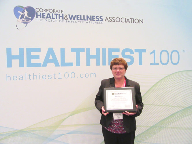 Submitted Photo Donna Trusso holds the award The Resource Center received for being named the 77th healthiest workplace in America.