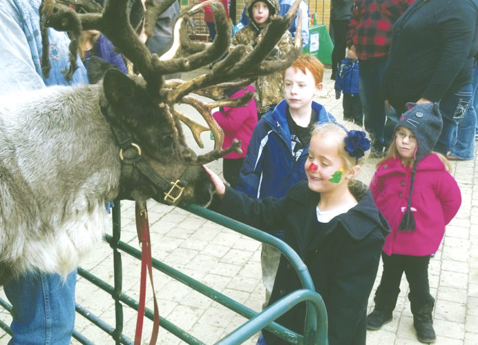 "Submitted Photo Past attendees of ""Christmas in the Park"" in Silver Creek visit with one of Santa's reindeer."