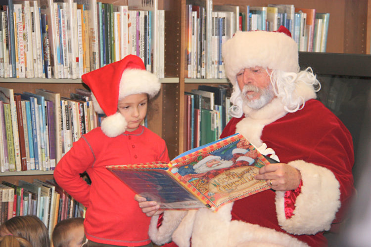"OBSERVER Photo by Tonja Dodd Holden Carlson of Sheridan listens to Santa read ""Twas the Night Before Christmas"" at Barker Library in Fredonia Saturday as part of the Miracle on Main Street event."