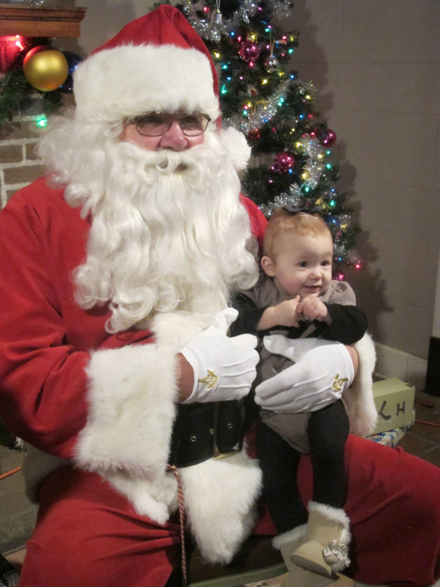 OBSERVER Photo by Nicole Gugino Addilynn Marsh, 10 months, sits on Santa's lap for the first time during the Kiwanis of Silver Creek's Christmas in the Park.