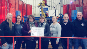 Submitted Photo Toys for Tots coordinators Heather Brown, left, and Terri Johnson hold a facsimile $2,000 check while posing with employees of Matco Tools' Jamestown plant. The money represents the amount Matco raised for Toys for Tots by raffling off two toolboxes.