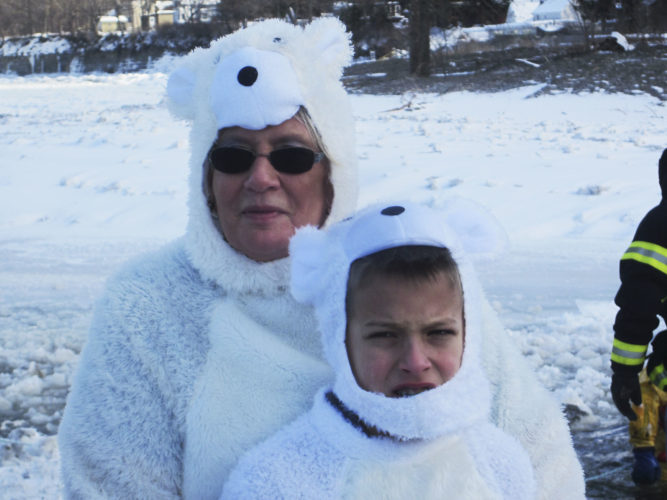 OBSERVER Photo by Diane R. Chodan Above: Co-organizer of the Polar Bear Swim Judi Kelly and her grandson Jackson Golembiewski get ready to lead the swimmers into the cold water. Kelly has gone into the water all 16 times the event has run, and she said this was the coldest in memory. Because of the necessity to clear the area, the swimmers plunged in smaller groups and got out quickly.