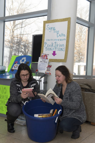 Submitted Photo Veronica Arce (left) and Katerina Koutsandreas sort through a handful of books donated during the final days of the Sigma Tau Delta book drive to benefit students in the seventh grade classroom of Fredonia graduate Rachel Beneway, who now teaches in New York City.