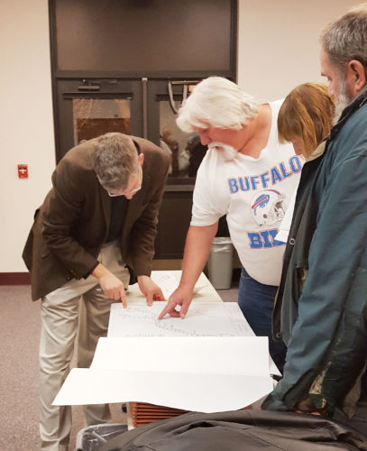 OBSERVER Photo by Nicole Gugino. Clark Patterson Lee Engineer Eric Wies (left) shows town of Dunkirk property owners plans for their properties during construction of the Route 5 regional waterline project in order to garner easements to their properties.