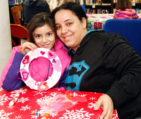 OBSERVER Photo by Tonja Dodd Third-grader Elena Ramos shows off her completed Valentine's Day wreath with her mother, Heidi Munoz, at the Dunkirk Free Library as part of the monthly free children's craft and activity morning.