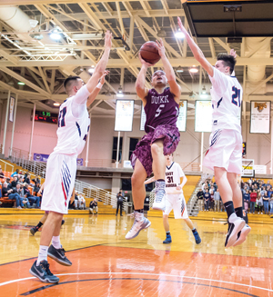 OBSERVER Photo by Ron Szot Dunkirk's Evon Hernandez (5) goes up for a shot between East Aurora's Joe Montgomery and Nick Montgomery during Monday's Section VI Class B1 semifinal game at Buffalo State.