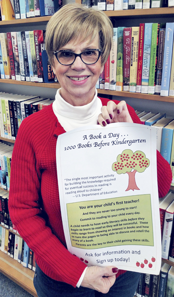 """Submitted Photo Interim Library Director Linda Beach displays an informational poster about the new early literacy program, """"1000 Books Before Kindergarten,"""" now being offered at Anderson-Lee Library."""