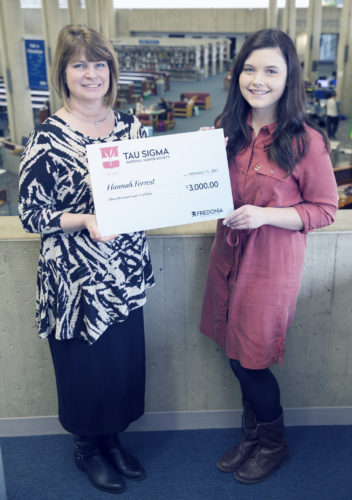 Submitted Photo Hannah Forrest (right) holding a symbolic Tau Sigma check with Helen Leysath, advisor to Tau Sigma and transfer coordinator at Fredonia, in Reed Library.