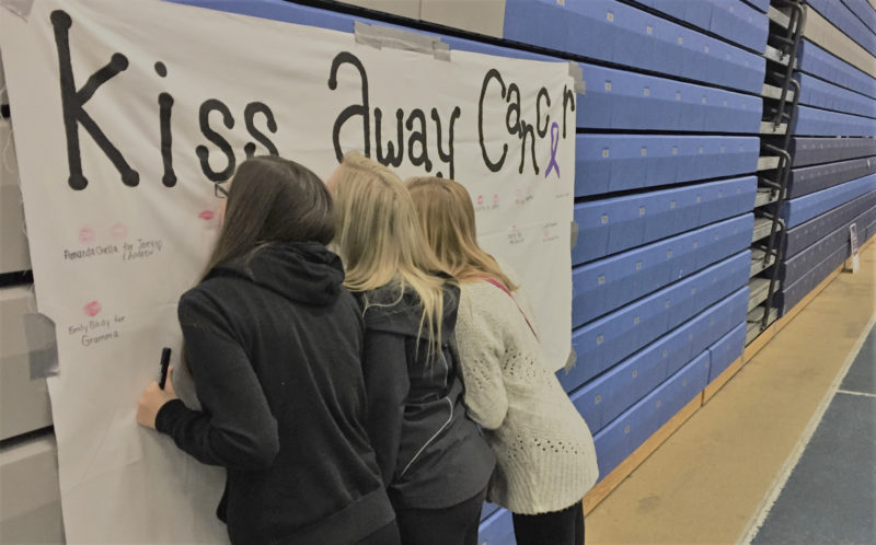 "OBSERVER Photo by Jordan Patterson  Fredonia students Michelle Hamilton, Hannah Koellner, and Emily Beers kiss the ""Kissing Away Cancer"" banner."