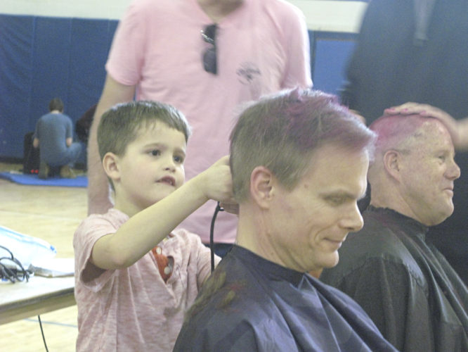 OBSERVER Photos by Amanda Deide At top left, Dr. Mary Rockey, principal, left, shaves the head of kindergarten teacher Valerie Gelsimino. At top right, Fifth-grade teacher Wade Dellow had his hair shaved off by Xavior Green. Fredonia Central School District board member Heath Forster had his temporarily-pink locks shaved off by Jackson Stahley.
