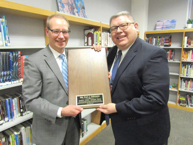 OBSERVER Photo by Greg Fox Fredonia Board of Education President Michael Bobseine (left) presents outgoing Superintendent Paul DiFonzo with a plaque to be hung on the Wall of Honor — once a picture is placed on it.