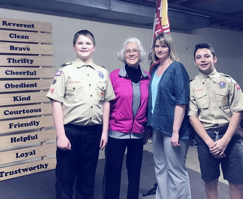 "OBSERVER Photo by Vicki Notaro Standing next to the Boy Scout Law characteristics are four of the people most involved in the ""Do a Good Turn Daily Challenge,"" left to right: Scout Justin Powell, resident Virginia Nedvesky, Training Coordinator Heidi Powell, and Scout Jacob Thompson."