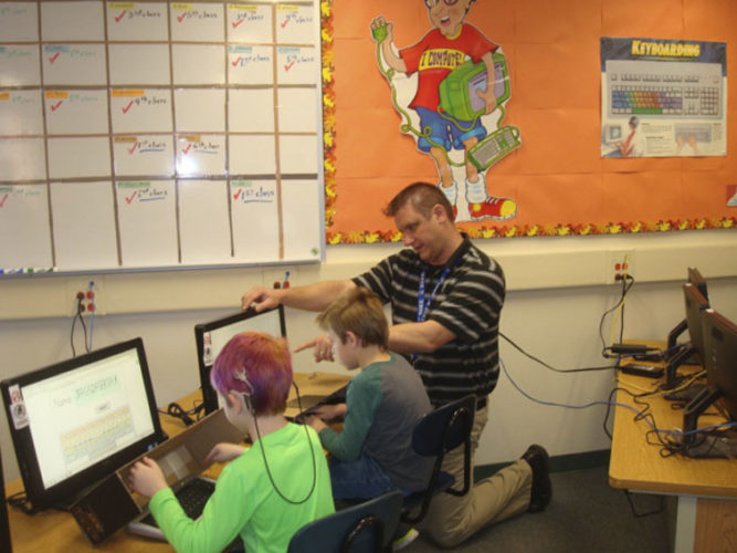Teacher Mark Putney, giving computer instruction to 2nd grade students Henry Conroy (right) and Jazz Witkowski.