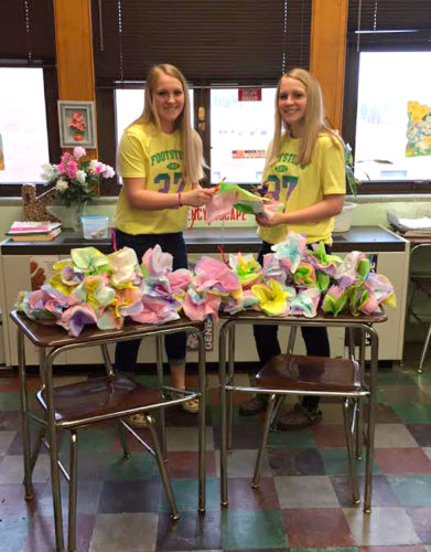 Submitted Photo. Cassadaga Valley Key Club members Kaitlyn Dahl and Hailey Dahl hold up tissue-paper Easter flowers they helped to make, along with over 20 other Key Club members. This project was made possible by a grant from the Northern Chautauqua Community Foundation. The students will be delivering 70 of these flowers to the Heritage Village nursing home this week to bring some sunshine to the residents. The club is co-advised by Cathy Smith and Karen Schrader.