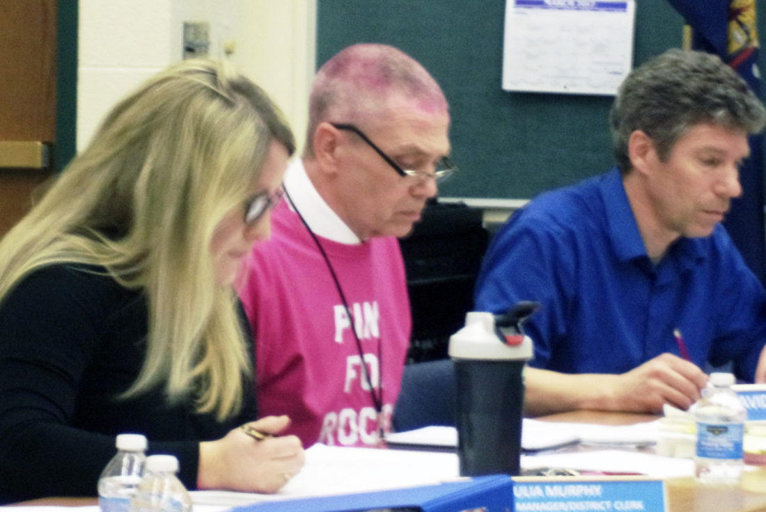 Photo by David Prenatt: WACS business manager Julia Murphy and Superintendent David Davison review budget items at the board of education supplemental meeting. Davison had his head shaved earlier that day as part of the Razors for Rockey fundraiser.