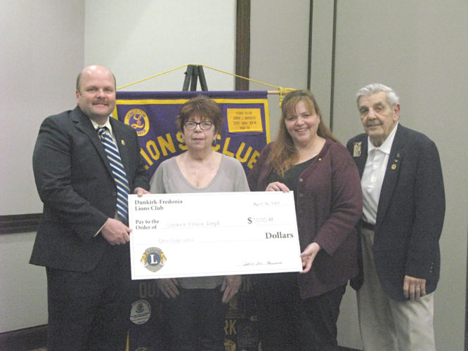 OBSERVER Photo by Amanda Dedie. From left, Lt. Mark Timmerman of the Dunkirk Police Department accepts a check for $1,000 in honor of the late Roy Marvin, alongside Marvin's wife, Kathy; July Cole, Dunkirk-Fredonia Lions Club president; and John Banach, current Lion and former district governor.