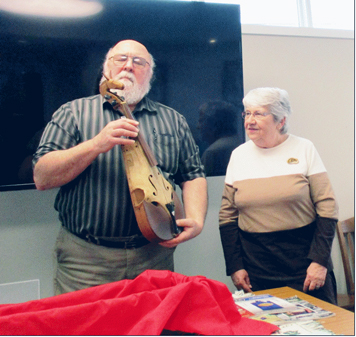 "Submitted Photo Vince Martonis gently handles Amos Sottle's Horse-Skull Fiddle as he explains its parts for Tuesday Club President Dianne Goodrich. He also described many historical items that he introduced as ""Hard to find things in small towns."""
