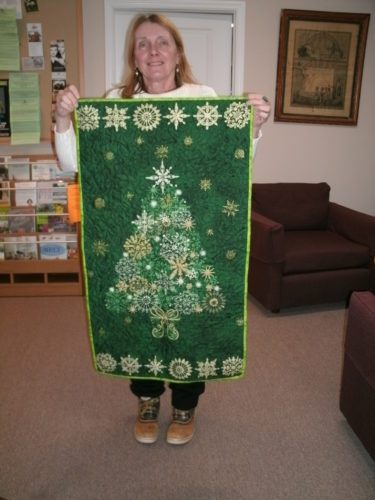 Assistant librarian Maggie Ruth holding the Christmas quilted wall hanging being raffled at the Kennedy Free Library. Submitted photo