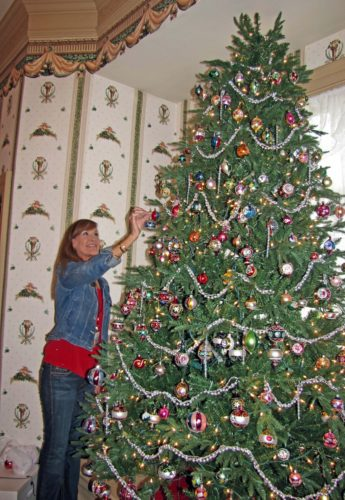 Volunteer docent Beth Tarpley decks the boughs of a Christmas tree at McClurg Museum with ornaments from an extensive collection donated by Marlin Casker of Jamestown. The 12-foot tree is in the parlor of the McClurg mansion in Westfield, one of five rooms on the first floor elaborately decorated for the holiday open house, which is from 2-4 p.m. Dec. 11. Submitted photo