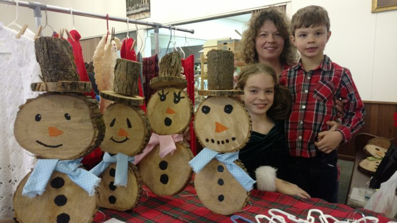 Katrina, Melissa and Luke Scheme look over the items available for sale at their display during the Craft Show and Cookie Walk, held at the Cherry Creek/ Leon United Methodist Church ad part of the Christmas in Cherry Creek last weekend.