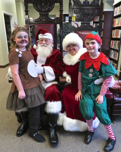 "Santa and Mrs. Claus visited the Randolph Library where children could sit with them and share their Christmas Wish Lists. Shown with the jolly couple are Adeline and Owen Wright who participated in the elementary school play, ""Rudolph the Red-Nosed Reindeer."""