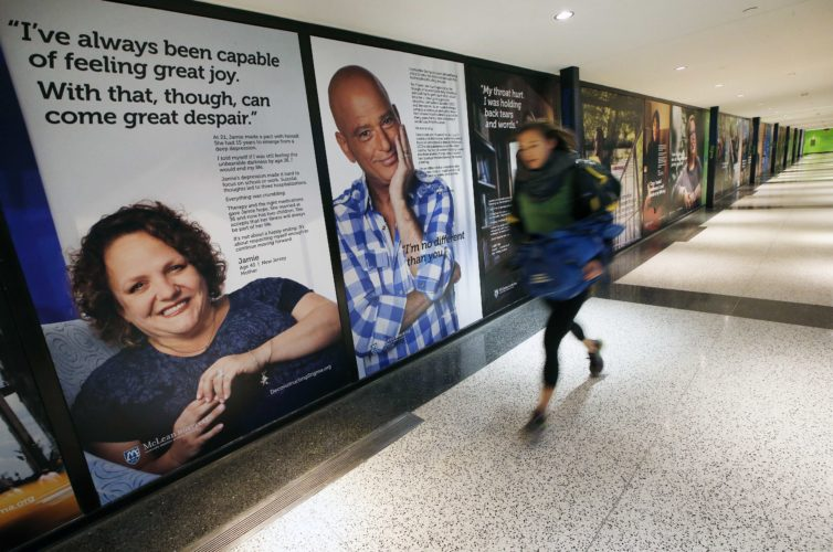A passenger rushes past an art exhibit at Logan International Airport in Boston, Dec. 8. The exhibit consists of larger-than-life posters of nearly three dozen people — some ordinary, some famous — who have struggled with mental illness. AP photo