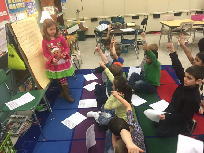 Fletcher Elementary School first grader, Briar Cercone, shows her class how she used a number line to solve a word problem.  The students on the rug are showing her a thumbs up if they agree with her strategy, a thumbs down if they disagree and raising their hand if they would like to add on to her thinking as part of a Math Talk.