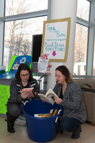 Veronica Arce, left, and Katerina Koutsandreas sort through a handful of books donated during the final days of the Sigma Tau Delta book drive to benefit students in the seventh grade classroom of Fredonia graduate Rachel Beneway, who now teaches in New York City. Submitted photo