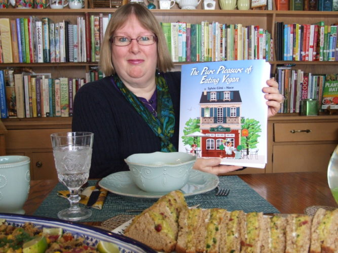 Sylvie Cote-Nace proudly holds her vegan cookbook, a result of her tireless effort. Her extensive cookbook library can be seen behind her. Pictured, counterclockwise,  Black Bean and Quinoa Salad with Chipotle Vinaigrette; Chickpeas and Kale Sandwich Spread with Sunflower Seeds and Cranberries served on 10-grain bread; and Split Pea and Green Lentil Soup with Greens. Photos by Beverly Kehe-Rowland