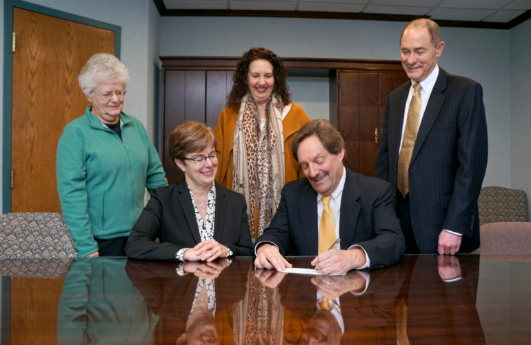 Peter Stark signs a check for the 2017 grants to UPMC Chautauqua WCA from WCA Foundation as foundation board members Cristie Herbst, Betsy Wright, seated, Melanie Gritters and James M. Smith watch the historic commitment of $537,797 to benefit our community's health care at WCA. Submitted photo by Joel Marsh, UPMC Chautauqua WCA