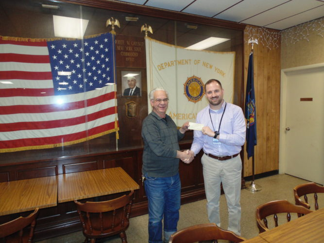 Southern Chautauqua County Club Associates recently donated $500 to the Chautauqua County Veteran Services Agency to support the veterans van. Every month, the van transports disabled veterans to the Buffalo VA Clinic. Legionnaire Gary Carvella presents Greg Carlson, county Veteran Services Agency director, with the check.  P-J photo by Jimmy McCarthy