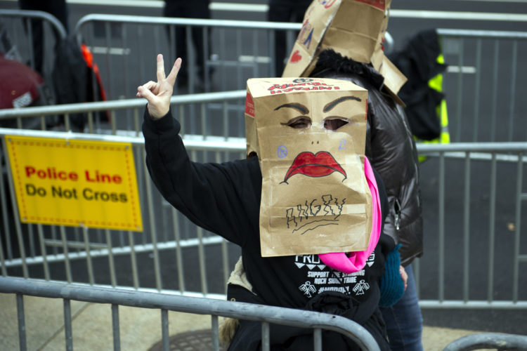 A protestor flashes the peace sign while walking along the presidential inaugural parade route in Washington, Friday, Jan. 20, 2017. (AP Photo/Cliff Owen)