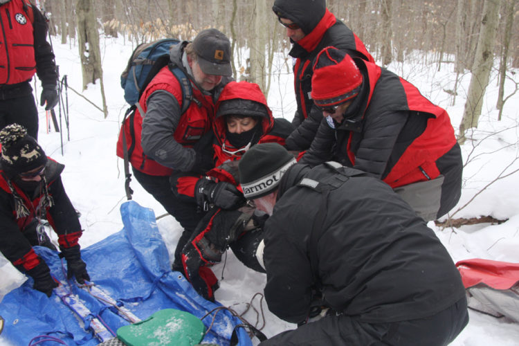 The patrollers carefully move the patient to the emergency sled. Photos by Deb Everts