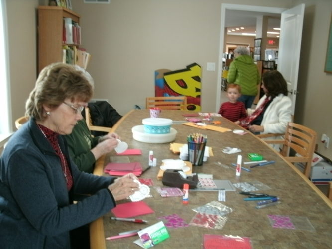 Sheila Hoene and others begin working on valentine cards for veterans at the Kennedy Free Library.