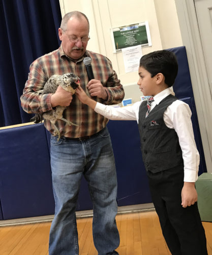 """Love Elementary School student, Angel Rosa, petted an Easter egg chicken that Vic Marcum from Marcum Farms brought into school as a part of presentation during the second graders' """"Cycles of Nature"""" unit."""