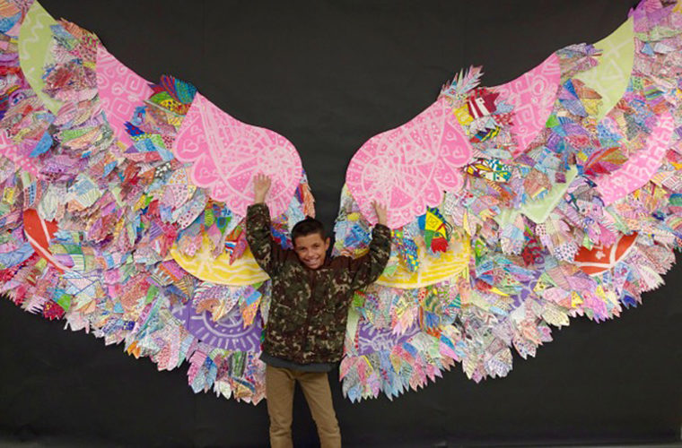 """Love Elementary School fourth grader, Alberto Serrano, stepped into Love School's art project, """"What Lifts You Up."""" The huge angel wings are made up of hundreds of feathers created by Love art students. The project was inspired by artist Kelsey Montague."""