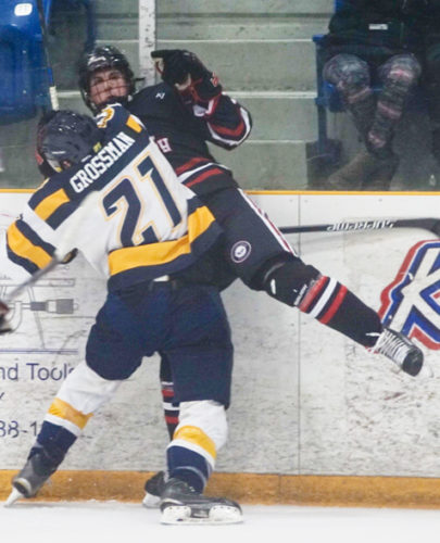 Southern Tier's Luke Grossman (21) checks a Pittsburgh player into the boards Friday evening at Northwest Arena. Photo by Chad Ecklof