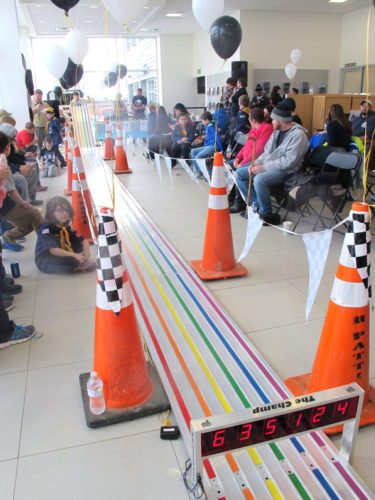Cub Scout Pack 115 members, families and friends gathered around the rainbow-colored track to watch the cars fly at the annual Jamestown Cub Scouts Citywide Pinewood Derby at Ed Shults Ford-Lincoln Showroom on Washington Street on Saturday.  P-J photo by Katrina Fuller