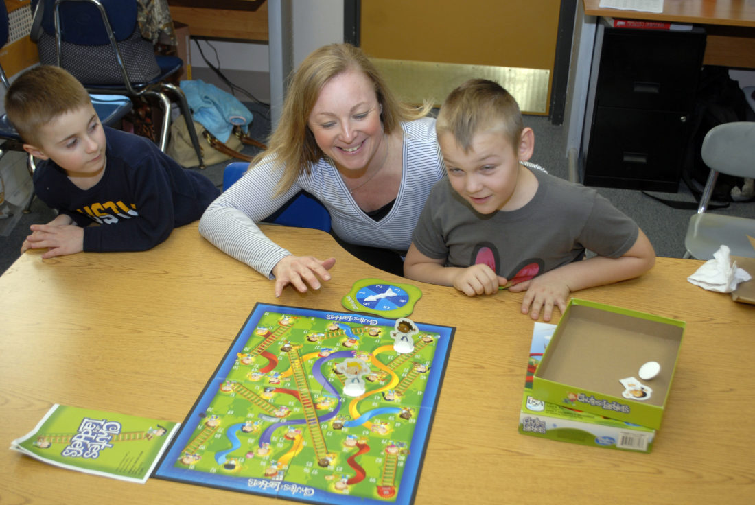 Toni Zebka-Waite, the Jamestown Area YMCA's Love's Terrific Kids site coordinator, youth worker and volunteer fire fighter is pictured here playing a board game with kids who are part of the Y-Kids program, in the Y's youth department, Feb. 23.
