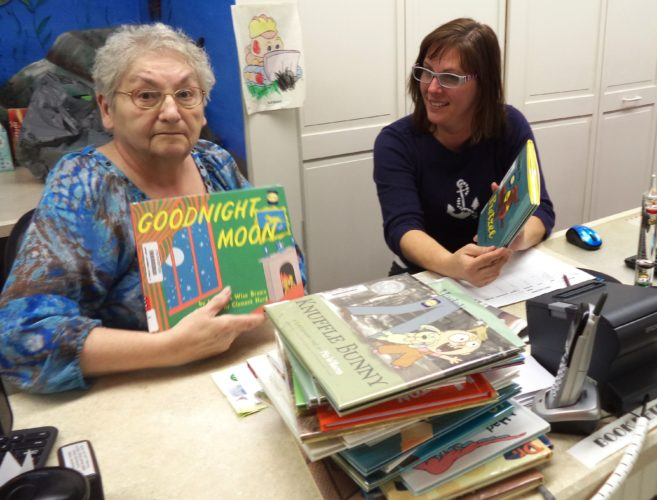 Findley Lake Library assistant director Joanne Malecki and director Melissa Froah, work to process some of the 100 children's books donated by the Brownstone Book Fund. P-J photos by David Prenatt