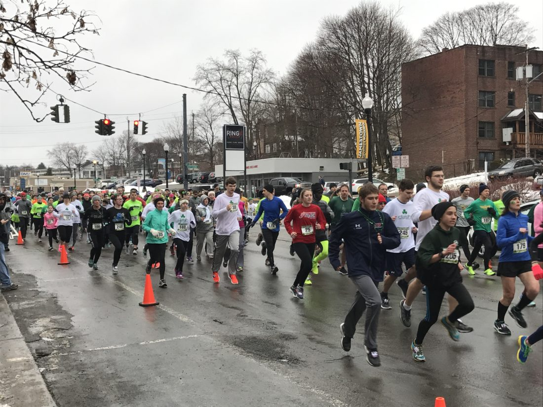 Runners take off from the start line just moments after David Reinhardt, Chautauqua Striders athletic director, sounds the alarm to kick off the annual St. Patrick's Day Dash. Despite the cold whether, a few hundred participants were ready to race on Saturday morning.  P-J photo by Katrina Fuller